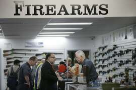 """In this Dec. 9, 2015, photo, sales associate Mike Conway, right, shows Paul Angulo a pistol at Bullseye Sport gun shop in Riverside, Calif. The massacre at Sandy Hook elementary school in which a mentally disturbed young man killed 26 children and teachers galvanized calls across the nation for tighter gun controls. But in the three years since, many states have moved in the opposite direction, embracing the National Rifle Association's response that more """"good guys with guns"""" are what's needed to limit the carnage of mass shootings. (AP Photo/Jae C. Hong)"""