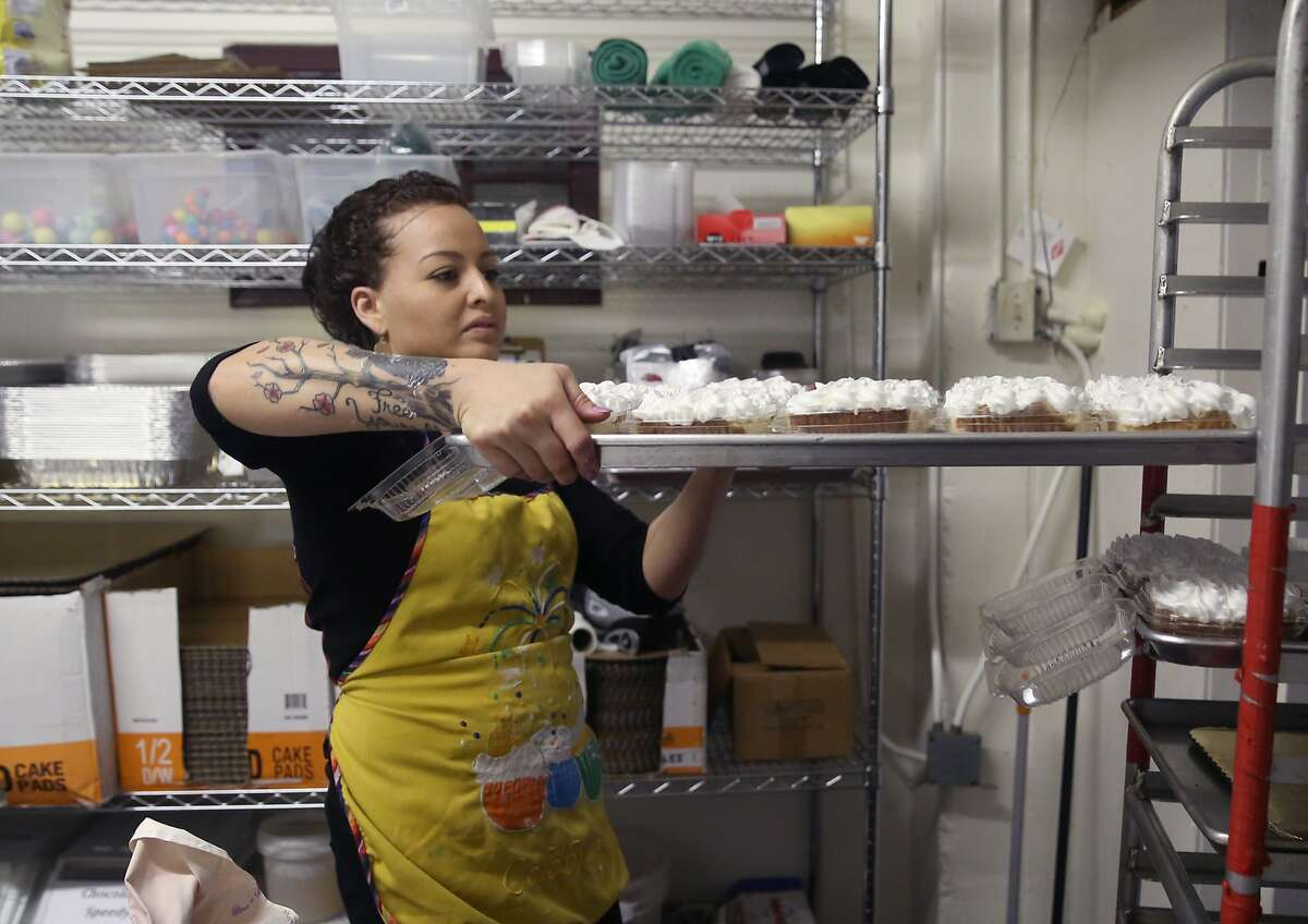 Decorator Sonia Fernandez moves a tray of tres leches cake, a traditional Christmas dessert, at Lelenita's Cakes San Francisco.