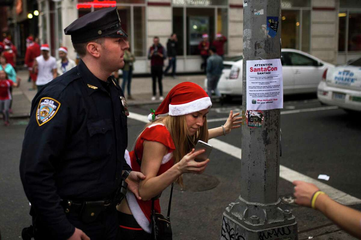 A police officer removes a reveler from standing on a post as they guard and clear the street of revelers dressed in holiday themed costumes during SantaCon in New York Saturday, Dec. 12, 2015, in New York.