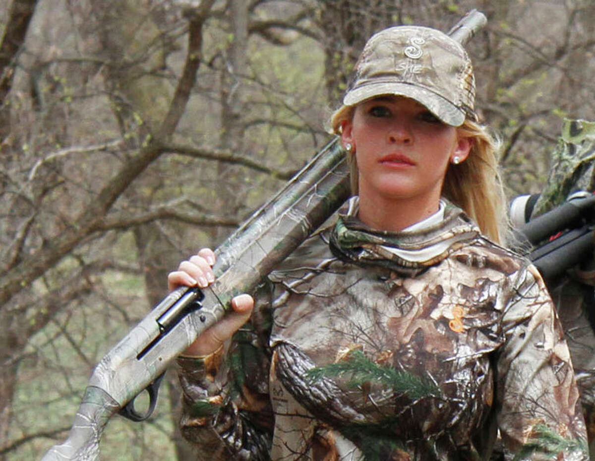 In this April 11, 2014, file photo, Theresa Vail walks with a hunting party in Chase County, Kan. Vail, a former Miss Kansas who hosts an Outdoor Channel adventure show, is accused of illegally shooting an Alaska grizzly bear and conspiring to cover up the violation, according to charges filed in a rural state court. (Michael Pearce/The Wichita Eagle via AP)