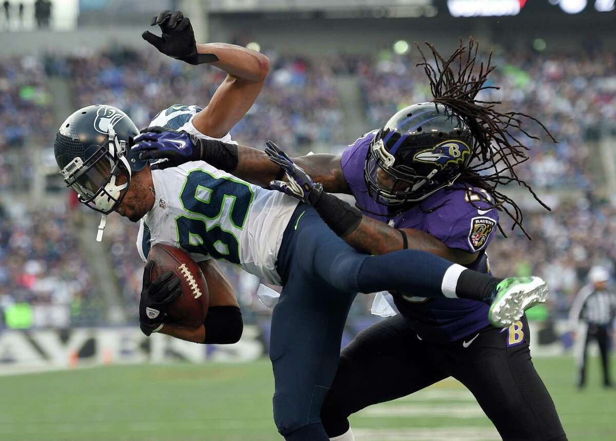 Seattle Seahawks wide receiver Doug Baldwin (89) is hit by Baltimore Ravens free safety Kendrick Lewis (23), as Baldwin scores a touchdown during the second half an NFL football game, Sunday, Dec. 13, 2015, in Baltimore. (AP Photo/Nick Wass)