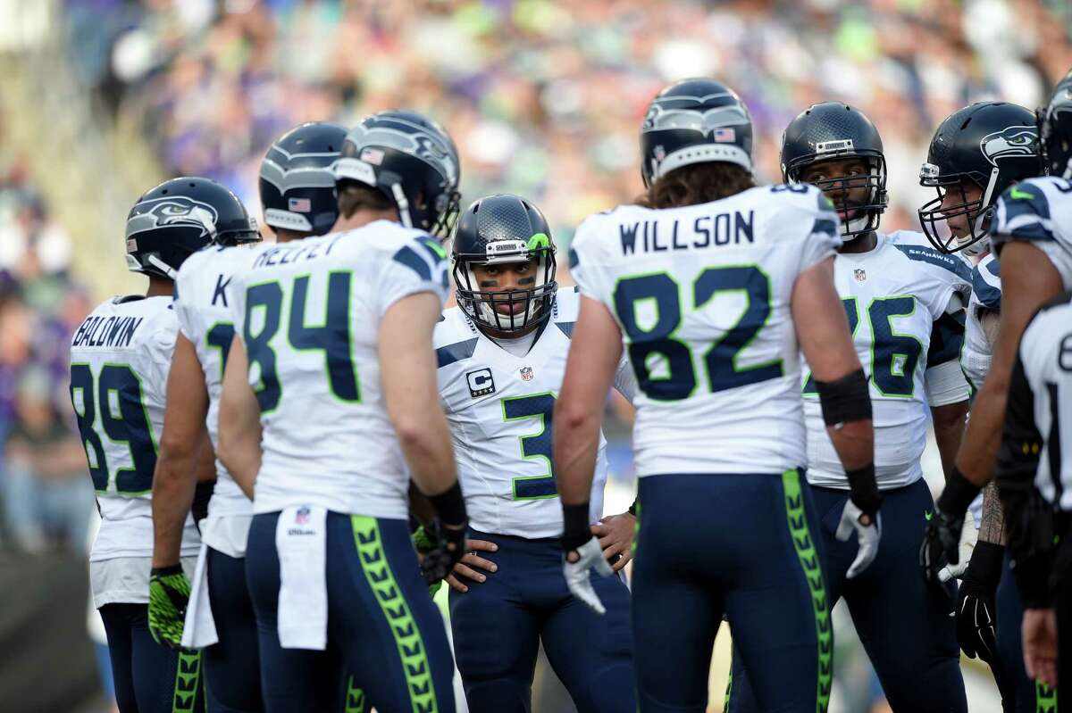 Seattle Seahawks quarterback Russell Wilson (3) huddles with the offense during the first half an NFL football game against the Baltimore Ravens, Sunday, Dec. 13, 2015, in Baltimore. (AP Photo/Nick Wass)