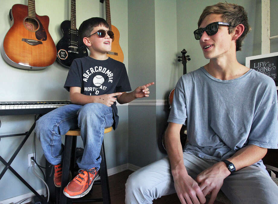 Hudson Simmons, left, and his older brother Conner Simmons have some fun in Conner's music room Dec. 3 as the two wear their special glasses to correct color blindness. Photo: Tom Reel /San Antonio Express-News / 2015 SAN ANTONIO EXPRESS-NEWS