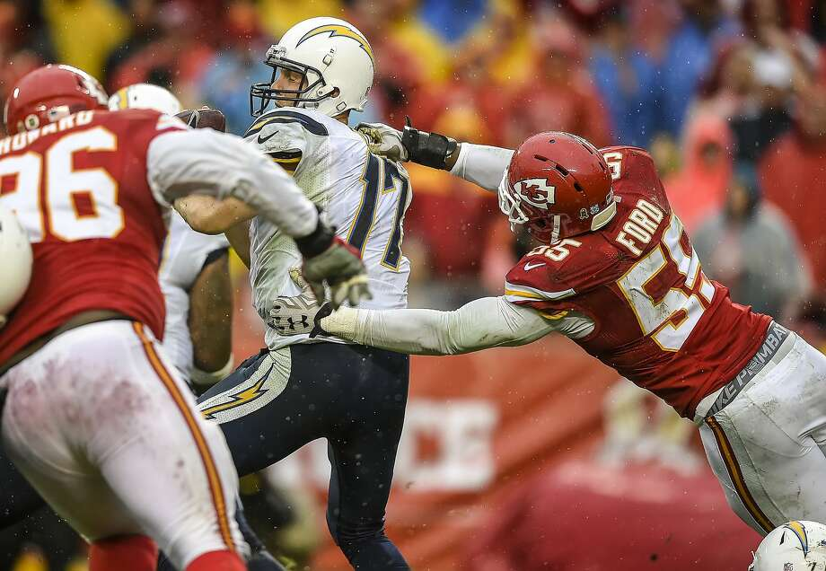 Chiefs linebacker Dee Ford pulls down the Chargers' Philip Rivers from behind for a third-quarter sack. Photo: David Eulitt, McClatchy-Tribune News Service
