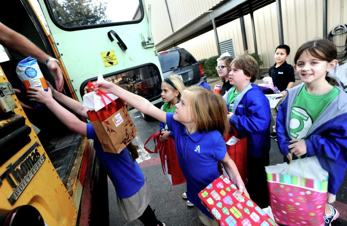 Students from Abilene Christian Schools load up gifts they have prepared for the families of children under 3, who receive services from the Betty Hardwick Center 's Early Childhood Intervention program Friday, Dec. 11, 2015, in Abilene, Texas. (AP Photo, Nellie Doneva/Abilene Reporter-News)