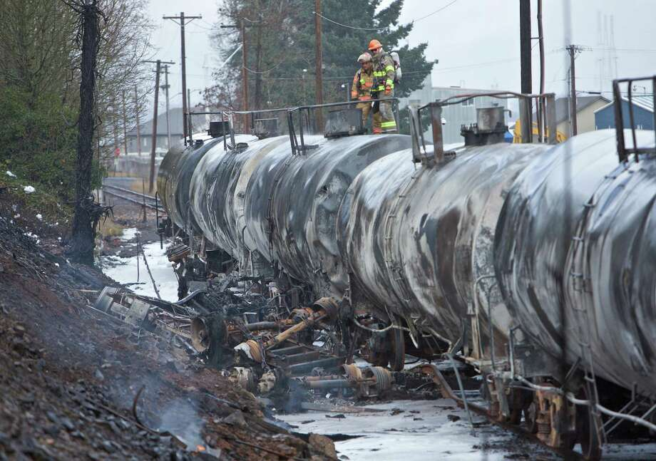 A fuel tanker truck crashed into railroad cars Sunday near the St. Johns Bridge in Portland, Ore. The crash killed the truck driver. , Sunday, Dec. 13, 2015. A semitrailer truck crashed on a roadway near a Portland railroad yard, sparking a railcar fire that sent up plumes of black smoke that were visible for miles. The truck driver was killed, Portland police said. (AP Photo/Craig Mitchelldyer) Photo: Craig Mitchelldyer, FRE / FR170751 AP