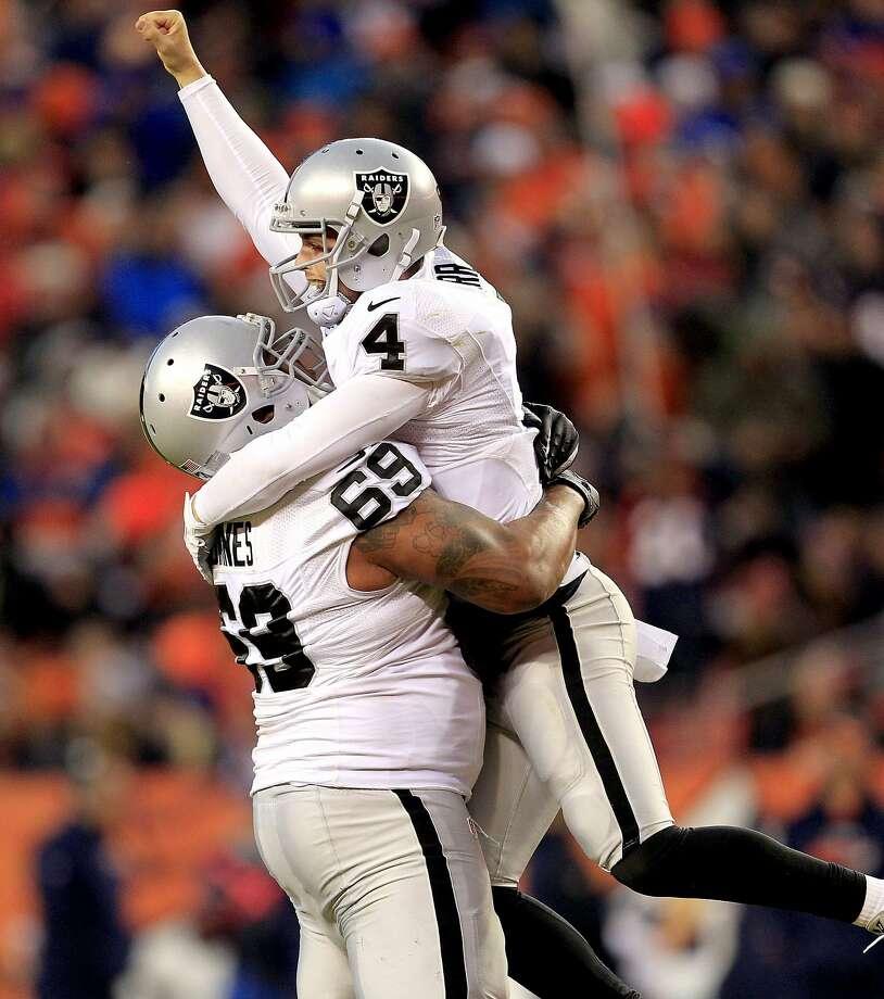 Derek Carr leaps on tackle Khalif Barnes to celebrate one of the Raiders quarterback's two second-half touchdown passes. Photo: Joe Mahoney, Associated Press