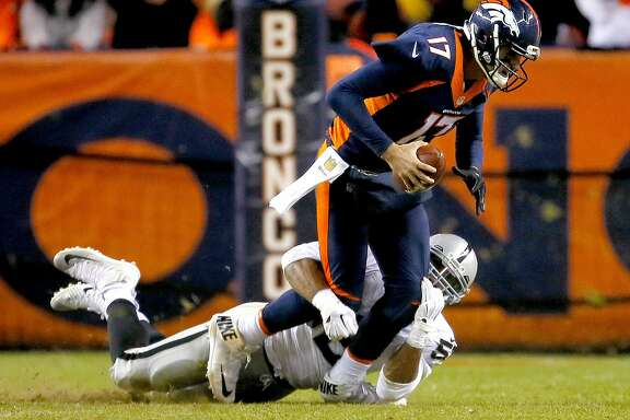 Denver Broncos quarterback Brock Osweiler (17) is sacked by Oakland Raiders defensive end Khalil Mack (52), bottom, during the second half of an NFL football game, Sunday, Dec. 13, 2015, in Denver. The Raiders won 15-12. (AP Photo/Joe Mahoney)