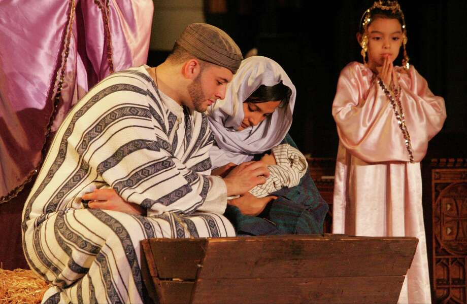 Joseph and Mary, as portrayed by Brandon Crespo and Kimberly Carvajal, hold the baby Jesus during St. John's Episcopal Church production of The Christmas Show in Stamford, Conn. on Dec. 13, 2015. Photo: Matthew Brown, For Hearst Connecticut Media / Connecticut Post Freelance