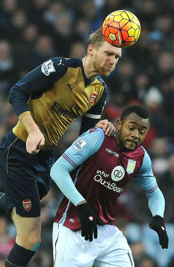 Arsenal's Per Mertesacker outjumps Aston Villa's Jordan Ayew during their English Premier League soccer match. Photo: Rui Vieira, Associated Press