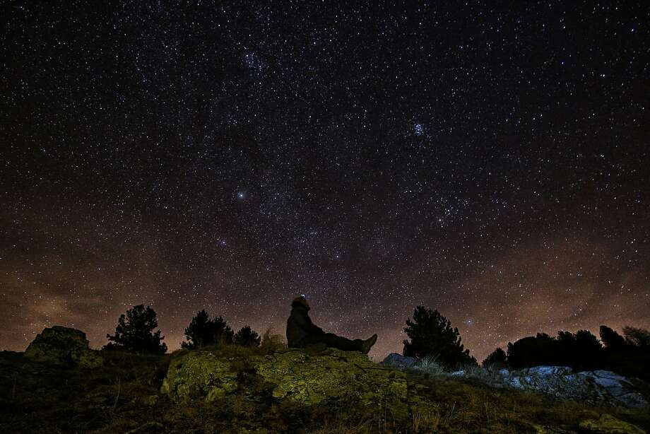 A photographer looks at the sky at night to see the annual Geminid meteor shower on the Elva Hill, in Maira Valley, near Cuneo, northern Italy on December 12, 2015.  Photo: Marco Bertorello, AFP / Getty Images