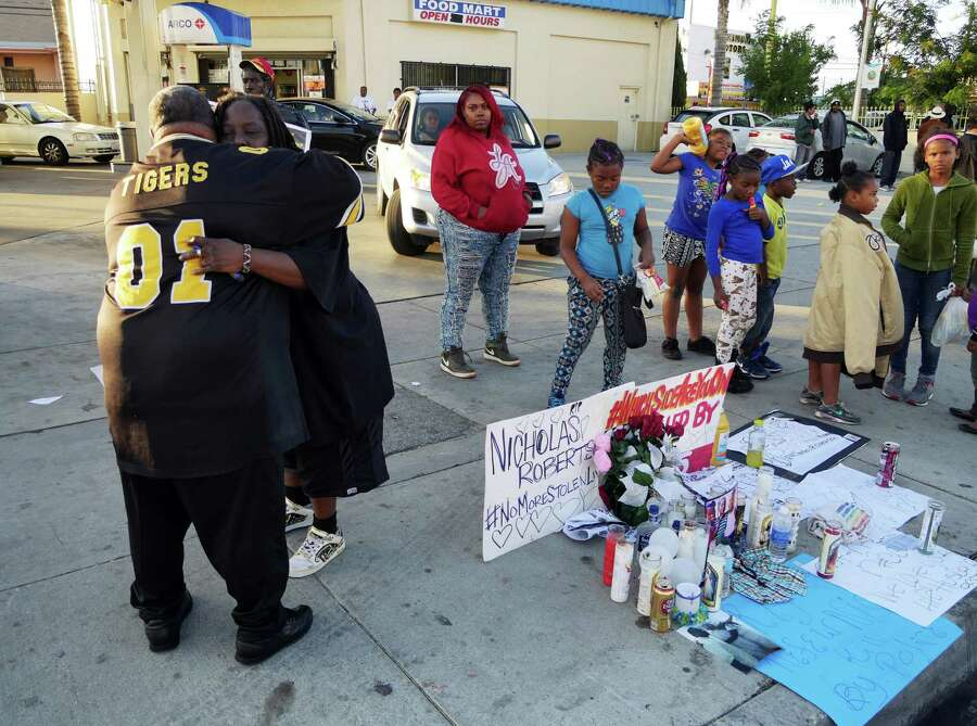 Latrice Barkus, Nicholas Robertson's aunt, is embraced in front of the sidewalk memorial set up to honor her nephew. Robertson was fatally shot Saturday by sheriff's deputies in Lynwood, Calif. Photo: David Martin /Associated Press / AP