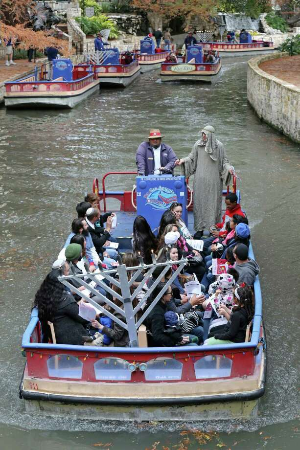 A barge takes people on a ride, the Menorah River Cruise. Hanukkah on the River had all the trappings of a fun-filled outing, including crafts, music and a play area. Photo: Edward A. Ornelas /San Antonio Express-News / © 2015 San Antonio Express-News