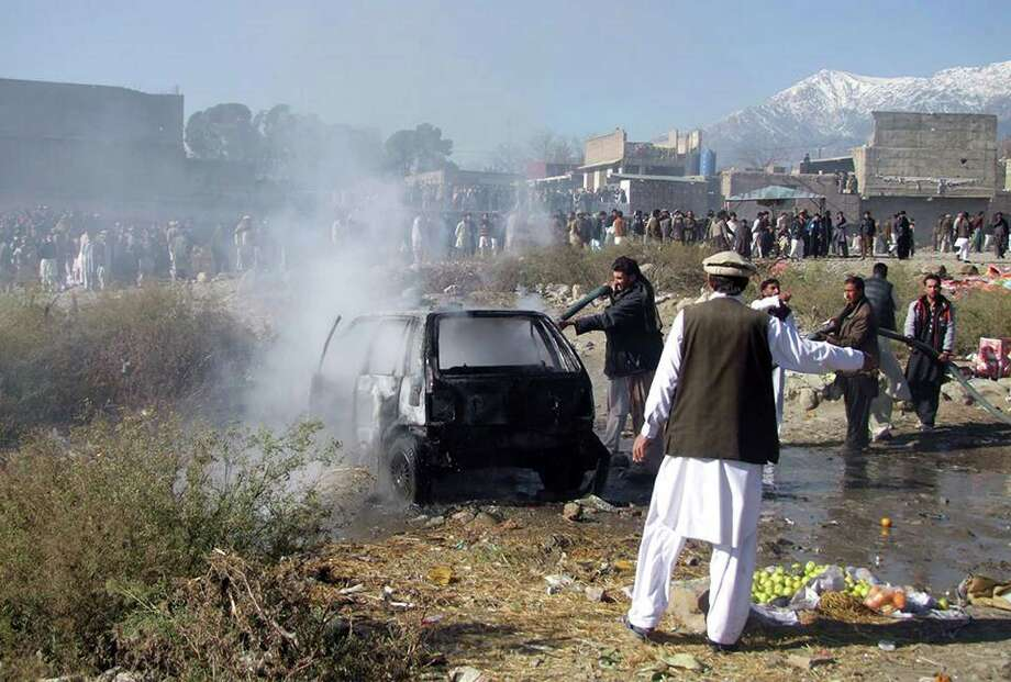 Pakistani firefighters extinguish a fire in a vechile at the site of a bomb explosion at a market in Parachinar, the capital of Kurram tribal district on December 13, 2015. Photo: M SAQLAIN /AFP / Getty Images / AFP