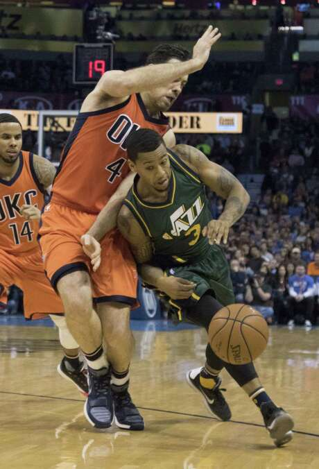 Jazz guard Trey Burke slides past Thunder forward Nick Collison. Burke finished with 10 points on 4-of-5 shooting. Photo: J Pat Carter, Stringer / 2015 Getty Images
