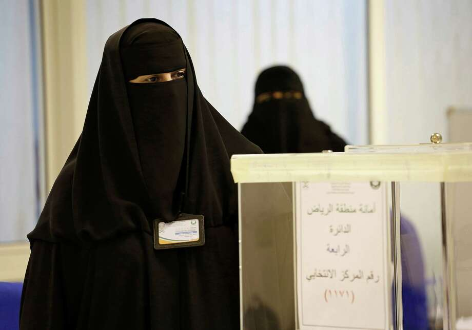 Voting poll volunteer Fatima Al-Druby, left, stands by as a voter from the 4th district drops her ballot in the box, with women going to the polls for the first time in the history of Saudi Arabia on Saturday, Dec. 12, 2015, in Riyadh. Of the 1.5 million registered voters, only 130,000 are women. (Carolyn Cole/Los Angeles Times/TNS) Photo: Carolyn Cole, MBR / McClatchy-Tribune News Service / Los Angeles Times