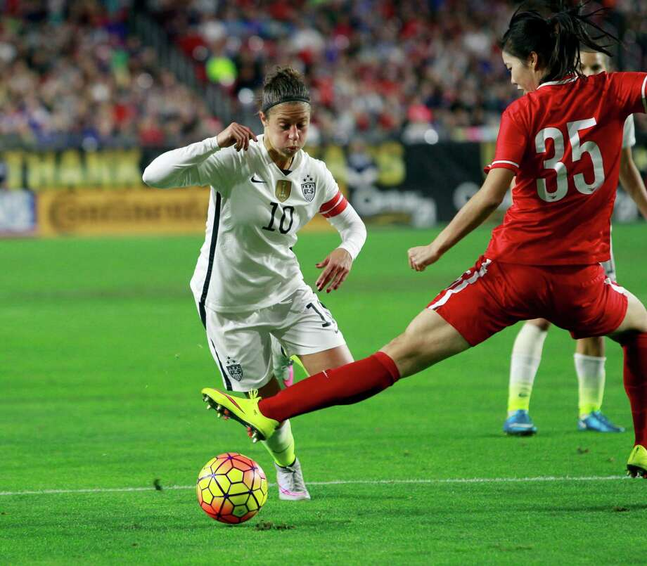 China's Yang Man gets full extension in a bid to stop a run by Carli Lloyd during the Americans' victory. Photo: Ralph Freso, FRE / FR170363 AP