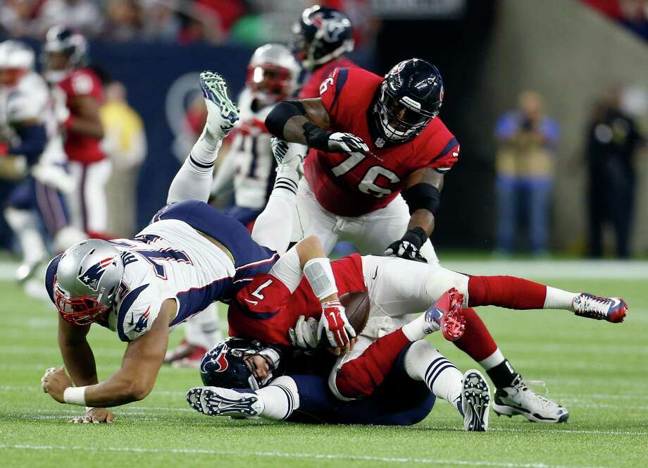 Patriots defensive ends Akiem Hicks, left, and Rob Ninkovich, obscured, team up to sack Brian Hoyer. The Texans allowed a season-high six sacks to the Patriots. Photo: Karen Warren, Staff / © 2015  Houston Chronicle