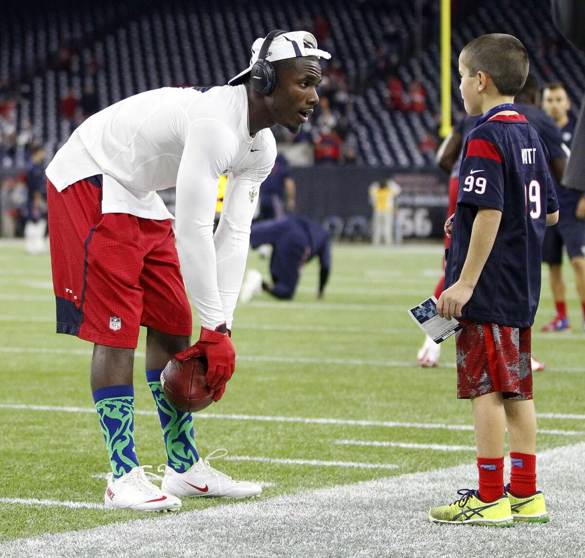 Houston Texans defensive back Charles James wears his new line of socks from Balitello Socks as he talks to a young fan before the start of an NFL football game at NRG Stadium on Sunday, Dec. 13, 2015, in Houston . ( Karen Warren / Houston Chronicle )