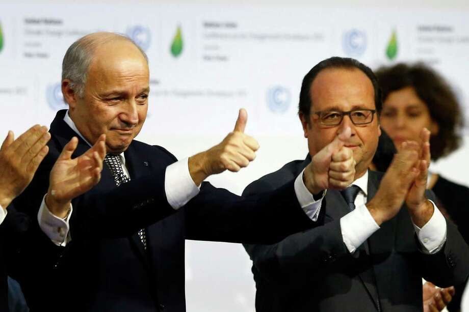 French President Francois Hollande, right, and French Foreign Minister and president of the COP21 Laurent Fabius react after the final conference at the COP21, the United Nations conference on climate change, in Le Bourget, north of Paris. Governments have adopted a global agreement that for the first time asks all countries to reduce or rein in their greenhouse gas emissions. Photo: Francois Mori /Associated Press / AP