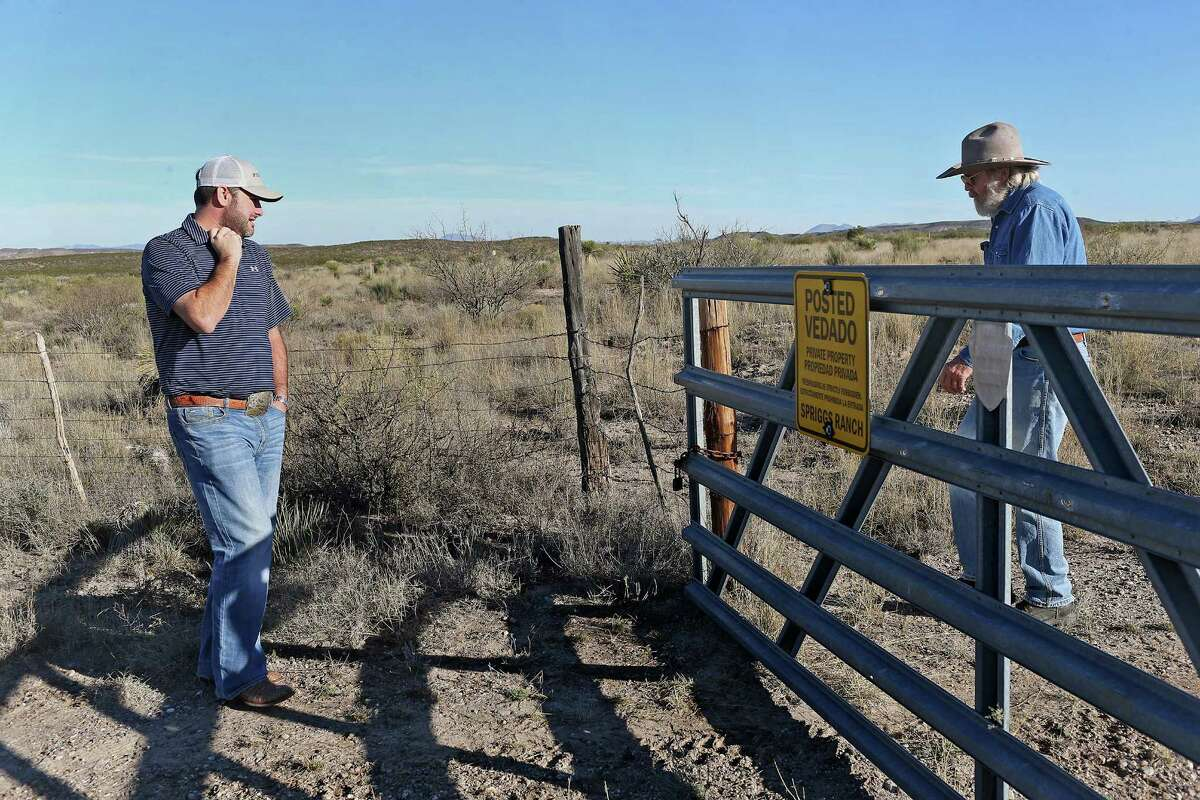 """Robert Jackson, left, waits as James Spriggs, 69, opens the gate of the family's 4,400-acre ranch south of Marfa, Texas in the Big Bend County Tuesday, Dec. 8, 2015. The Trans-Pecos Pipeline Project will run through the ranch and Spriggs spent months trying to fight the company but on advise from his lawyer, the family relented and let pipeline surveyors on his property this week. Jackson was with the surveying group. """"The oil companies and pipeline companies own Texas, and they do whatever they damn well please,"""" he said."""