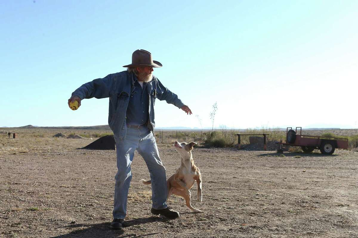 """James Spriggs, 69, plays with his dog, Sable, at the family's 4,400-acre ranch south of Marfa, Texas, Tuesday, Dec. 8, 2015. The Trans-Pecos Pipeline Project, which will transport natural gas from a collection site west of Fort Stockton into Mexico just upriver from Presidio, will run through part of the ranch. After months of fighting the pipeline, the family relented and let pipeline surveyors on his property this week. ?'The oil companies and pipeline companies own Texas, and they do whatever they damn well please,?"""" he said."""
