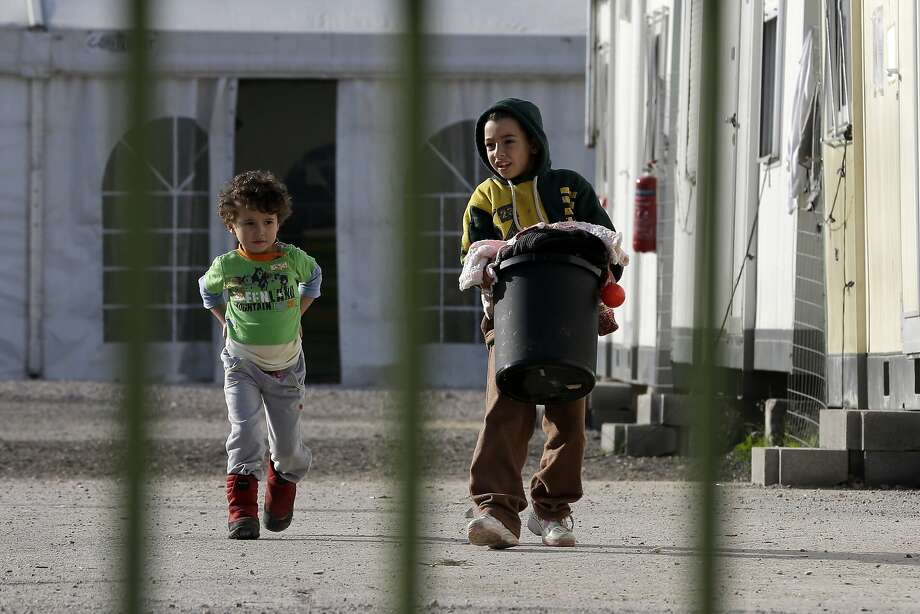 Children carry laundry at a refugee camp near central Athens. Financially stricken Greece is the main entry point for asylum-seekers trying to enter the 28-nation European Union. Photo: Thanassis Stavrakis, Associated Press