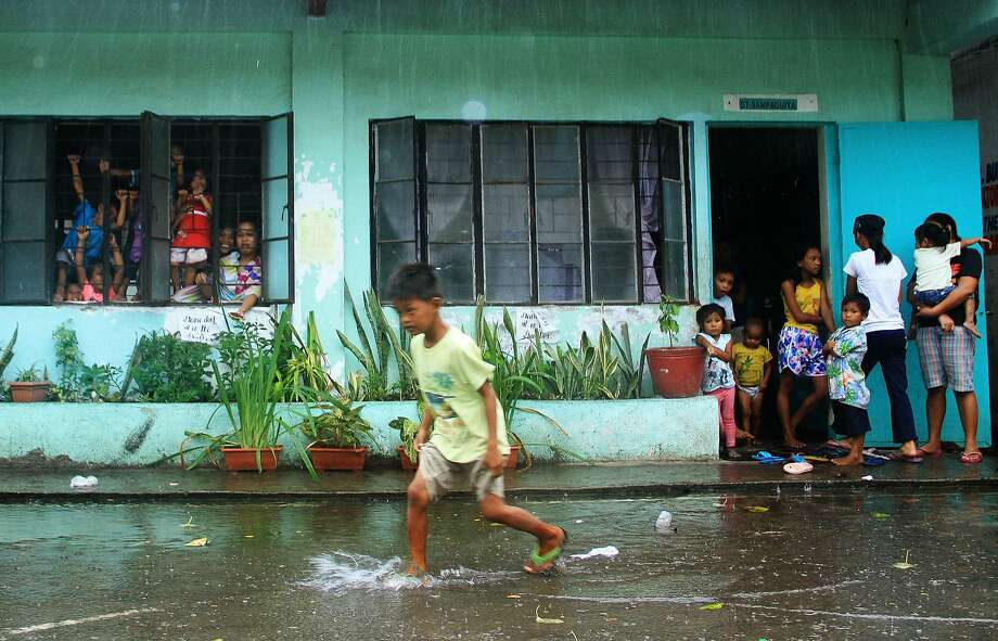 A young evacuee wades through flooded school grounds in the city of Legaspi in Albay province. Photo: Charism Sayat, AFP / Getty Images