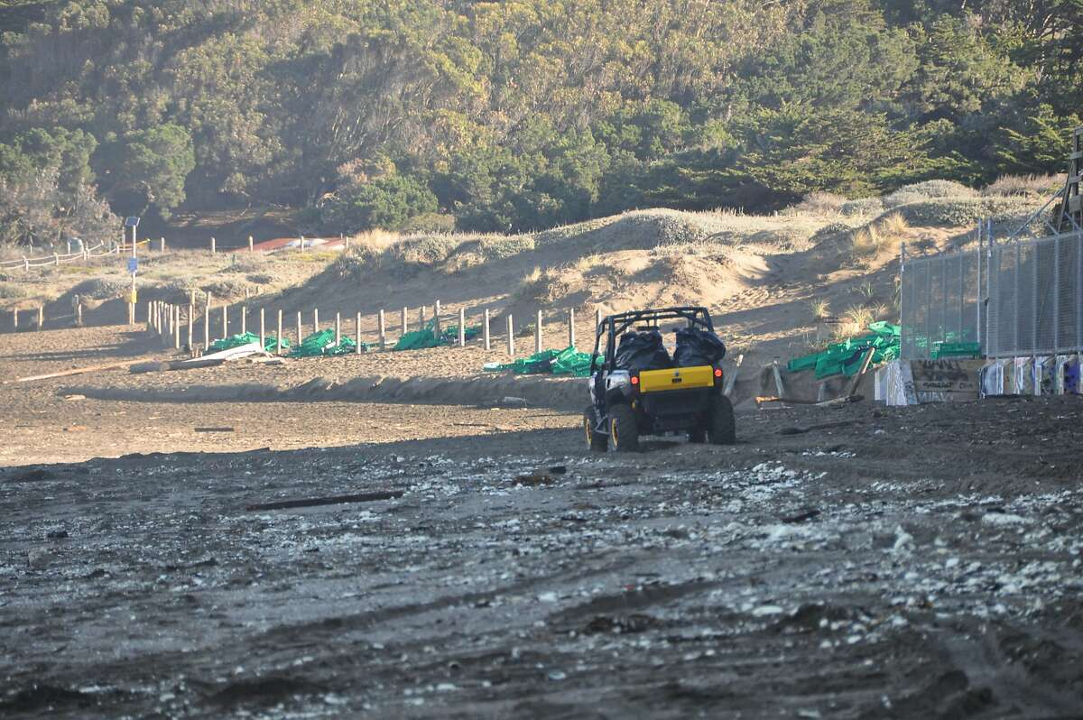 An all-terrain vehicle drives along Baker beach the morning of Dec. 14, 2015, as crews worked to clean up a mountain of debris after a container ship spilled some of its load in high seas.