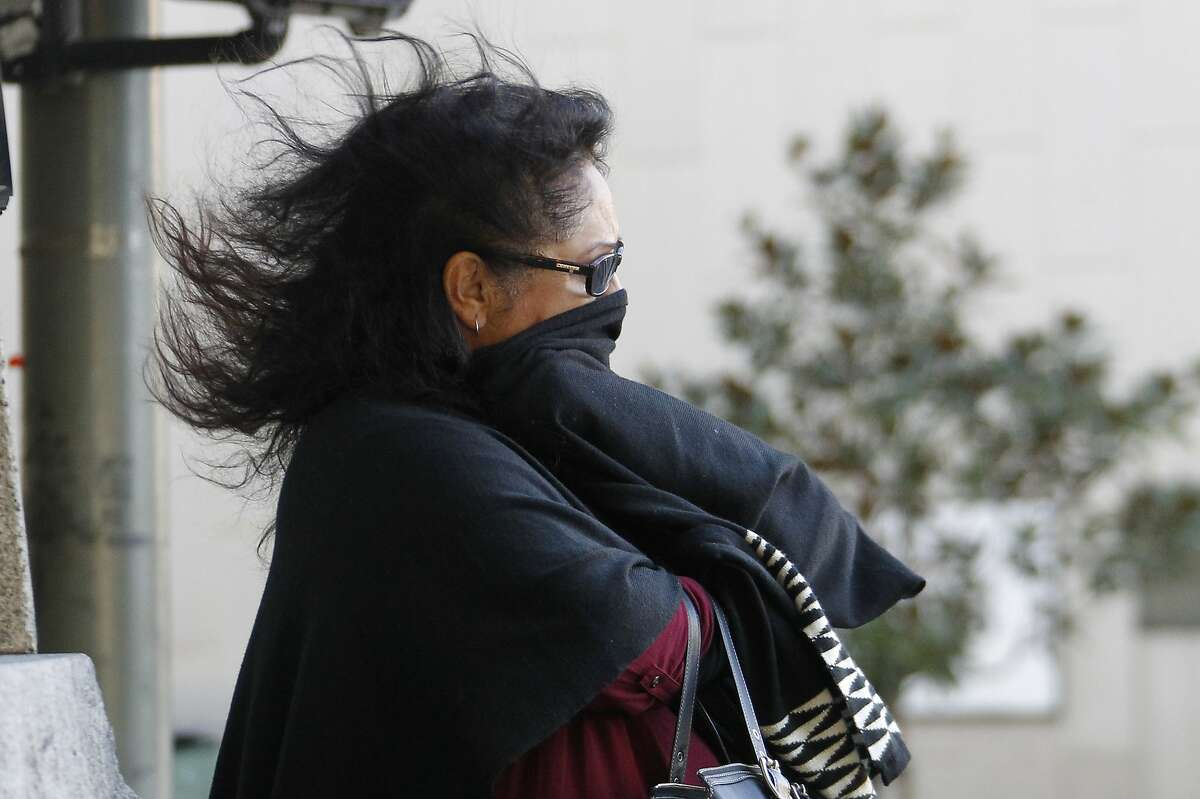 A pedestrian faces cold winds in downtown Los Angeles Monday, Dec. 14, 2015. A storm that dumped rain and snow across California moved out of the sodden state Monday, leaving behind cold temperatures, powerful winds and pounding surf. The National Weather Service said temperatures would be about 10 degrees colder than normal in Southern California and would barely top 60 during the day. (AP Photo/Nick Ut)