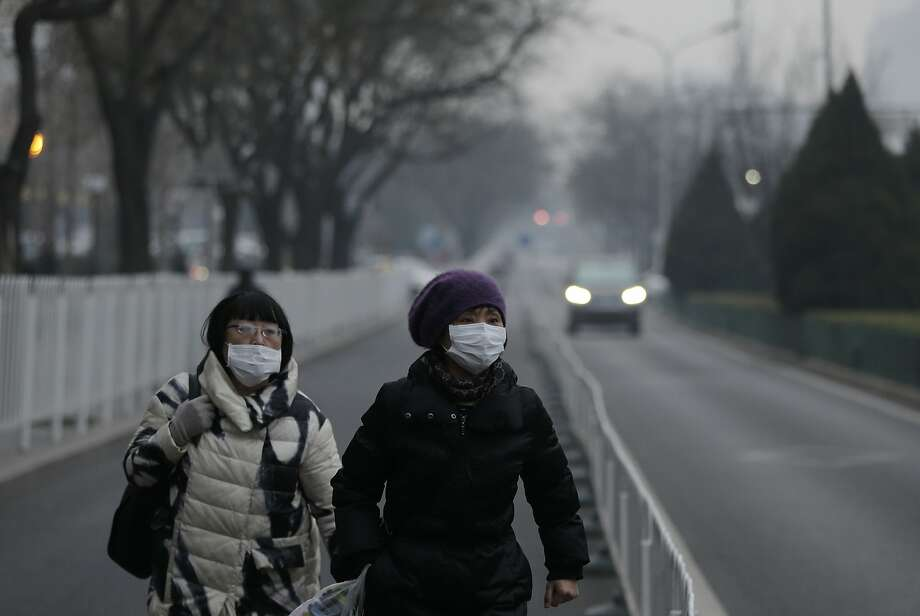Women wear masks as they walk along a street on a polluted day in Beijing, Sunday, Dec. 13, 2015. China's push for a global climate pact is partly because of its own increasingly pressing need to solve serious environmental problems, observers said Sunday. (AP Photo/Andy Wong) Photo: Andy Wong, Associated Press