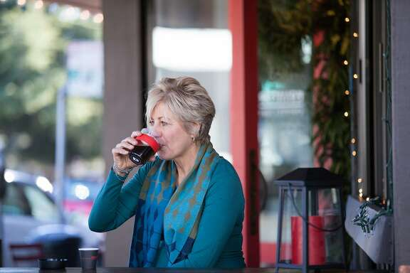 Helen Russell drinks coffee outside Equator Coffee, Monday, Dec. 14, 2015, in Mill Valley, Calif. Russell is one of the cofounders.