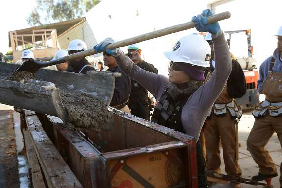 Student Marie Rowena Hall (right) learns to pour concrete to make a four foot wall at  JobTrain during laborers construction fundamentals training in Menlo Park, California, on Monday, December 14, 2015.