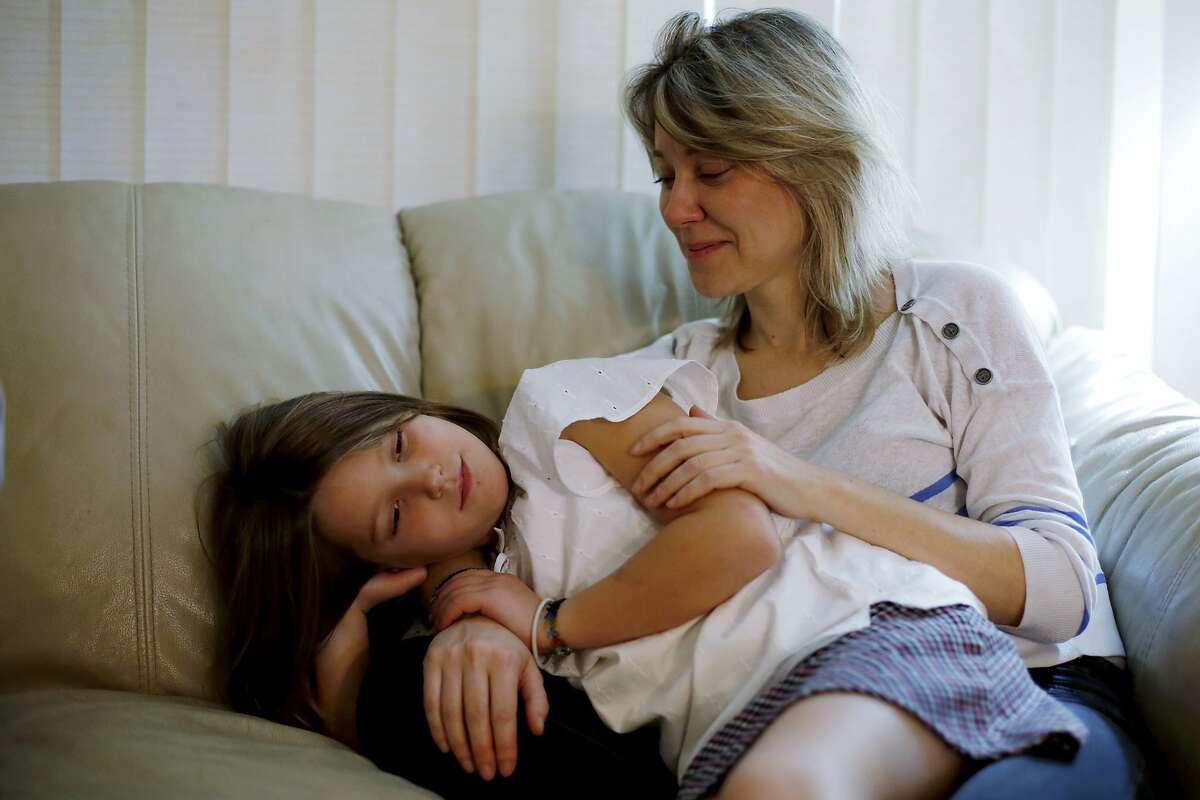 Natalia Kataeva sits with her daughter Lana, 8, at her apartment in Sunnyvale, California, on Sunday, Dec. 13, 2015.