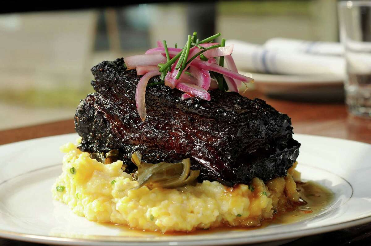 Beef belly burnt ends with cheese grits, braised greens and cane syrup at Southern Goods