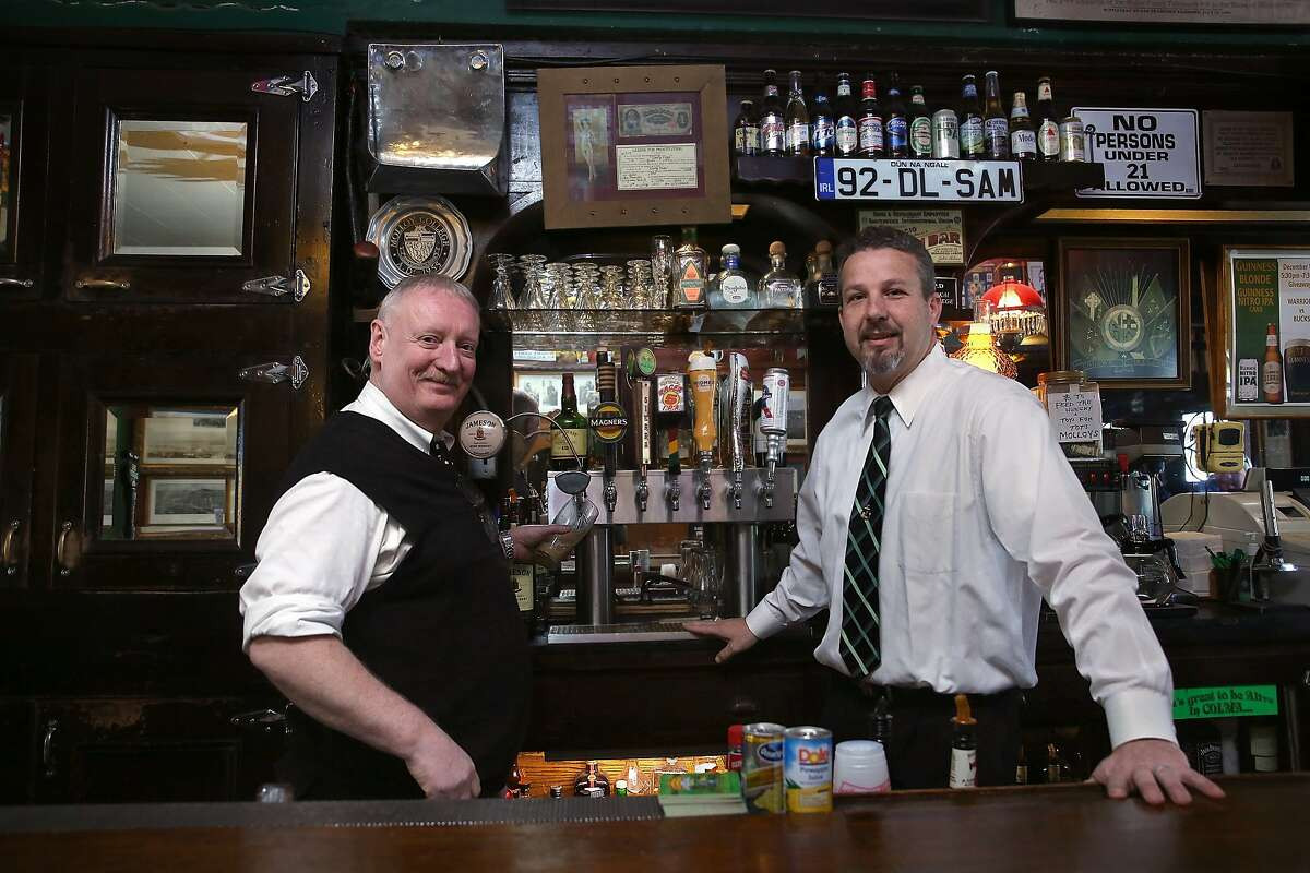 Long time bartender Pat Lane (left) and manager Owen Molloy (right) show Molloy's tavern in South San Francisco, California, on Friday, December 11, 2015.