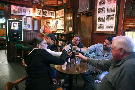 Clockwise--Longtime friends Rachelle Guillory, Joel Sandoval, Kevin McMahon, Javier Claudio, and Dan Mathiesen toast at Molloy's tavern in South San Francisco, California, on Friday, December 11, 2015.