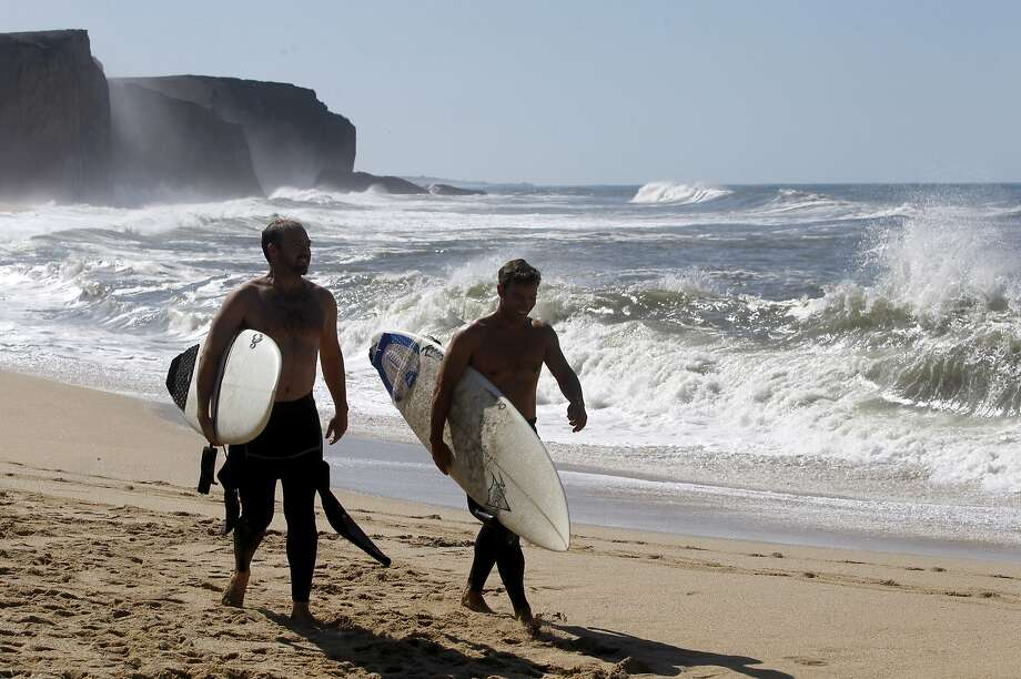 Surfers walk on Martins Beach in 2014 after a judge ordered Vinod Khosla to  unlock a