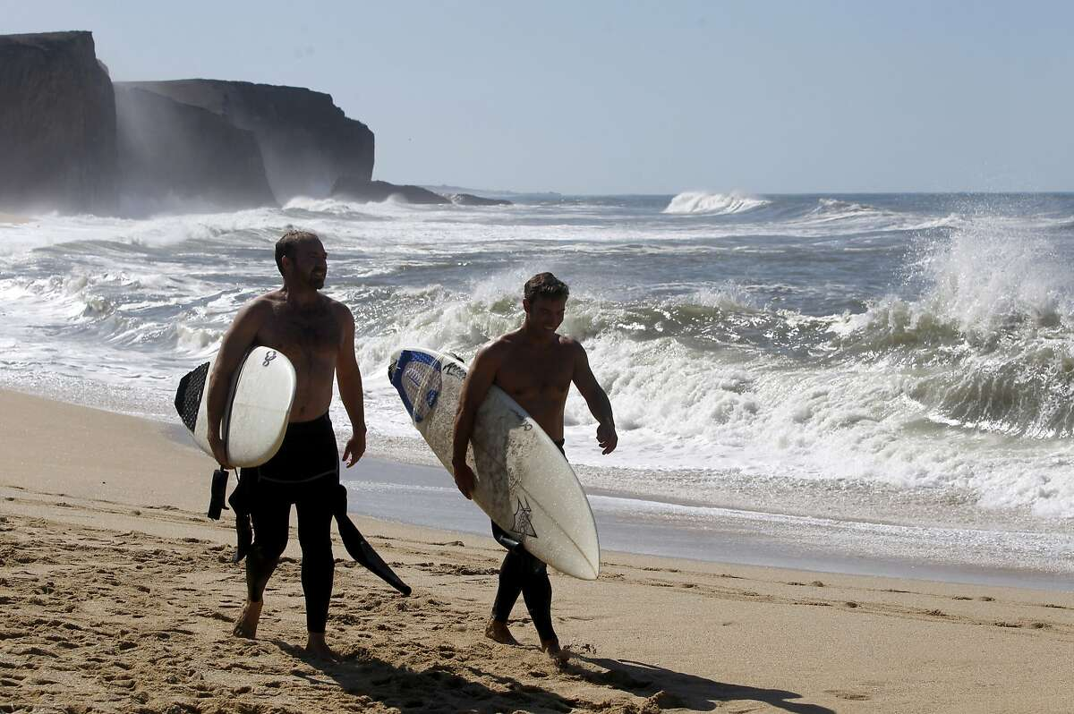 Tony Rose (left) and Jesse Quay walk on Martin's Beach after surfing in Half Moon Bay, Calif. on Thursday, Sept. 25, 2014, one day after a judge ordered landowner Vinod Khosla to unlock a private gate and allow public access to the beach.