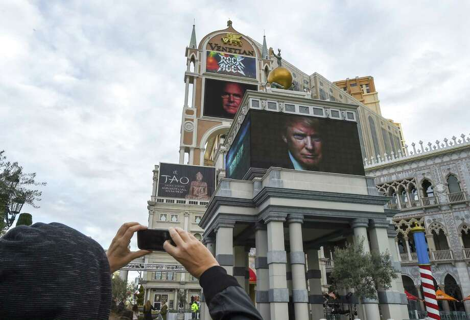 A tourist takes a photo of an electronic ad featuring Donald Trump, who'll be at center stage in tonight's CNN debate in Las Vegas. He'll be joined by Sens. Ted Cruz, Marco Rubio and Rand Paul; retired neurosurgeon Ben Carson; former Florida Gov. Jeb Bush; businesswoman Carly Fiorina; and Govs. John Kasich and Chris Christie. Photo: Robyn Beck /Getty Images / AFP