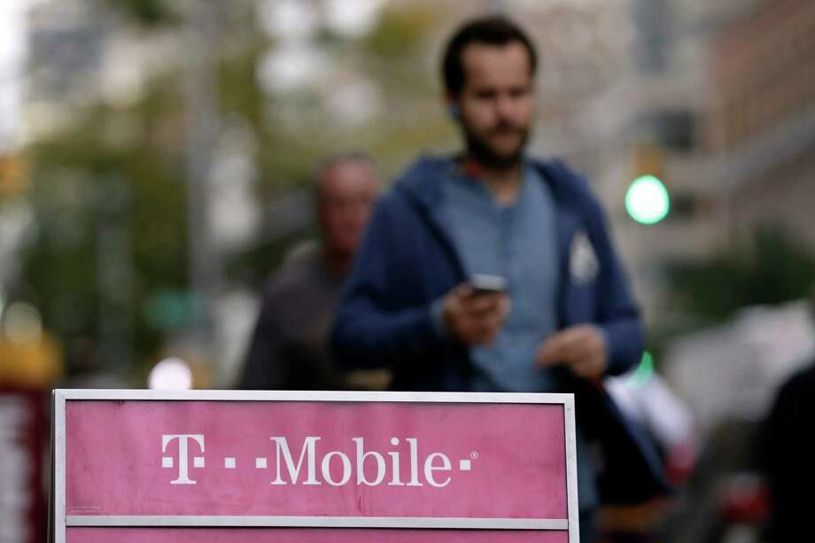 "FILE - This Oct. 14, 2015, file photo, shows people passing a T-Mobile store, in New York. The growing wireless carrier exempts major streaming music and, as of November, many popular video services from data limits on most of its plans. The company says the video providers don't have to pay for that, but do have to meet certain technical requirements to be included. YouTube and Facebook video aren't covered under this deal, called ""Binge On,"" because T-Mobile can't figure out if they are streaming video.  (AP Photo/Richard Drew, File) Photo: Richard Drew, STF / AP"