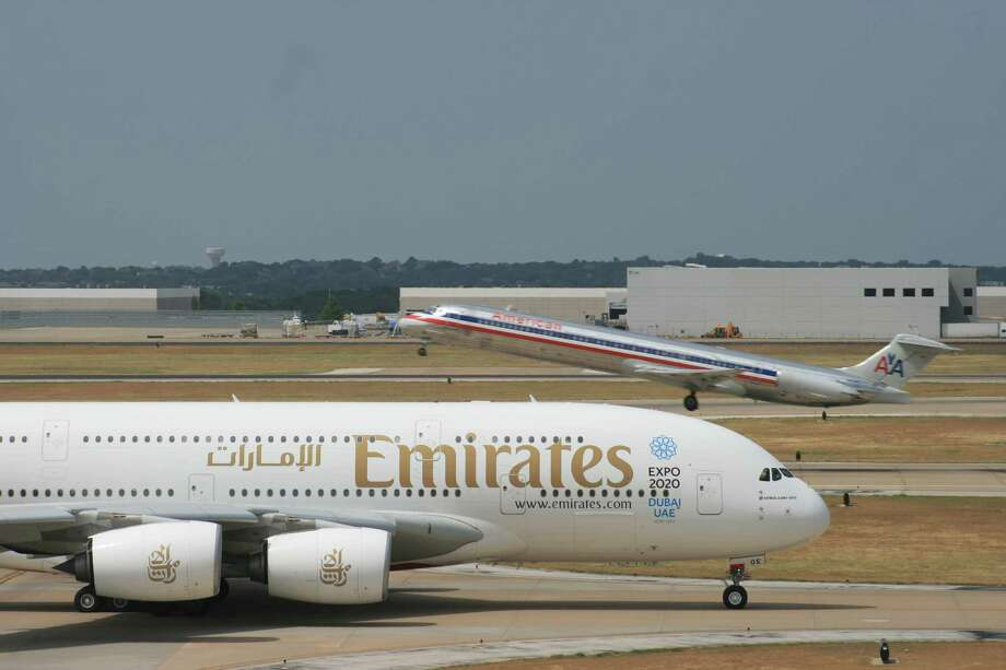 An American MD-80 takes off as an Emirates A380 taxis at DFW. Middle Eastern carriers are adding flights and destinations in the U.S. Photo: Bill Montgomery