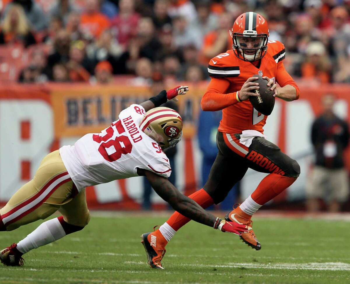Browns quarterback Johnny Manziel scrambles away from the San Francisco 49ers' Eli Harold before throwing an interception during the second quarter at FirstEnergy Stadium in Cleveland.