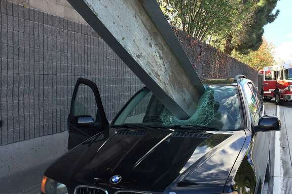 The driver of this BMW suffered only a small scratch after a beam fell off a flatbed truck and crashed through his windshield in San Jose, Calif.