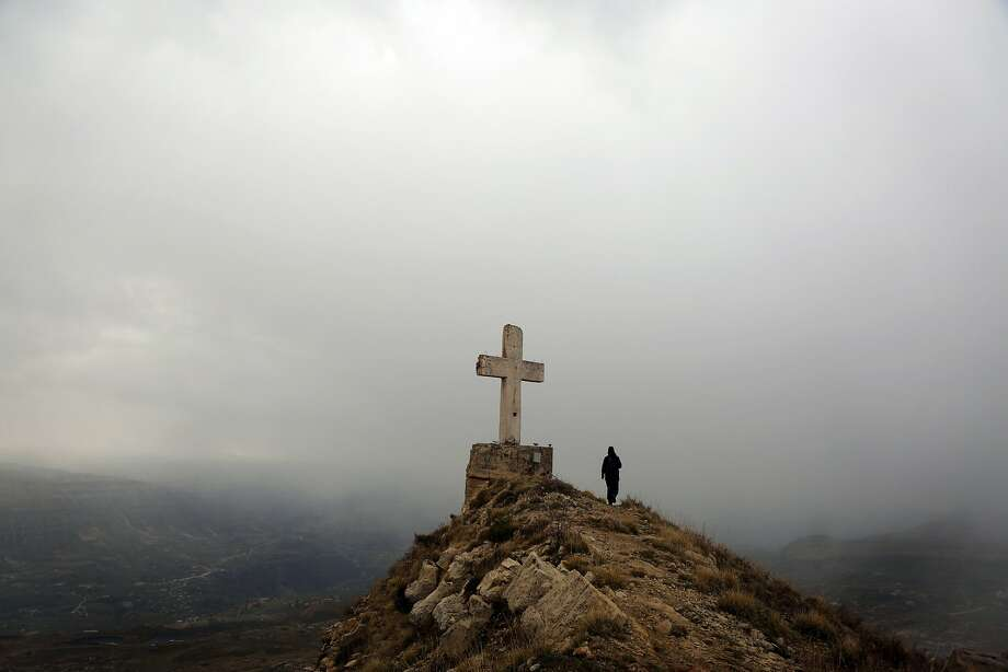 A Lebanese trecker takes a picture of a cross on a hilltop in the nothern ski resort village of Laklouk, 2000 meters above sea level in the Lebanese mountains north of Beirut, on December 13, 2015. Photo: Patrick Baz, AFP / Getty Images