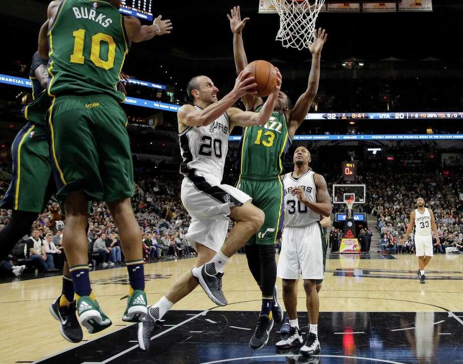 3863 x 3040~~$~~San Antonio Spurs guard Manu Ginobili (20) drives between Utah Jazz defenders Alec Burks (10) and Elijah Millsap (13) during the first half of an NBA basketball game, Monday, Dec. 14, 2015, in San Antonio. Photo: Eric Gay, AP / AP