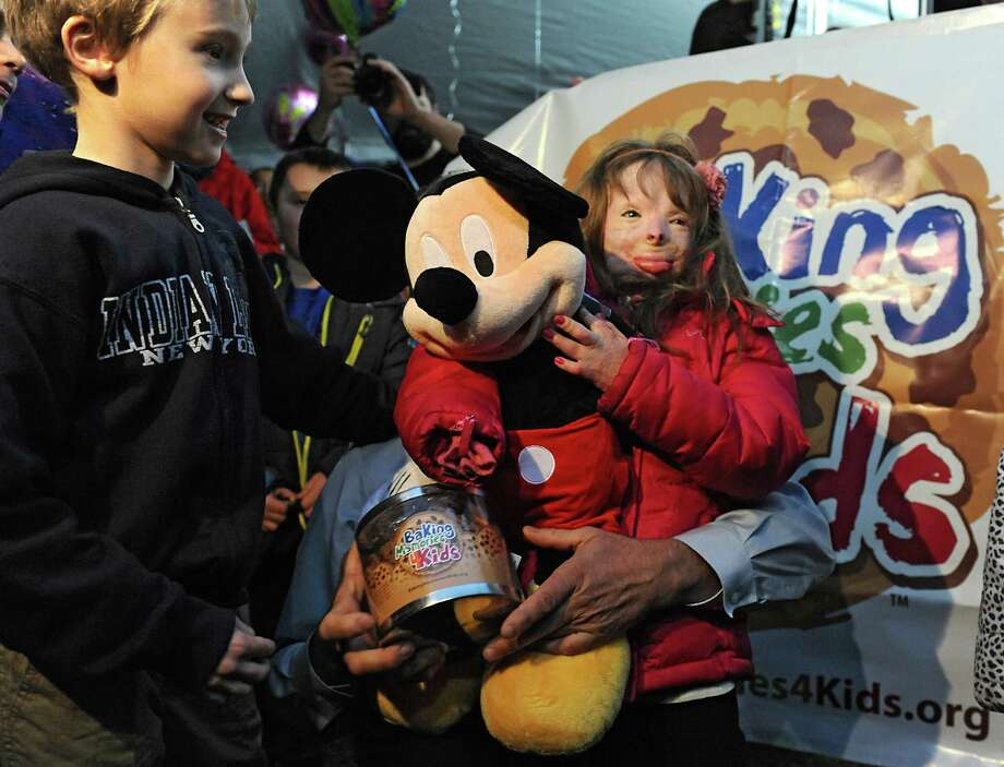 Baking Memories 4 Kids' Founder, Frank Squeo, behind Mickey Mouse doll, delivers an all expense paid trip to Florida theme parks to Sa'fyre Terry, right, and her family on Monday, Dec. 14, 2015 in Rotterdam, N.Y. Sa'fyre escaped a fire with burns over 75% of her body. The fire took the lives of her father and three siblings. Now 8, Sa'fyre is lovingly being cared for by her Aunt & Uncle and their children. Her friend Zach Cunniff, 7, left, looks on. (Lori Van Buren / Times Union) Photo: Lori Van Buren / 10034568A