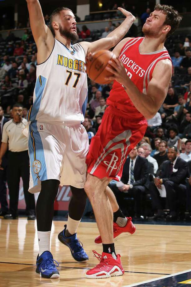 Donatas Motiejunas, right, who gave the Rockets 19 points in 22 minutes, takes a hit from Nuggets center Joffrey Lauvergne. Photo: Doug Pensinger, Staff / 2015 Getty Images