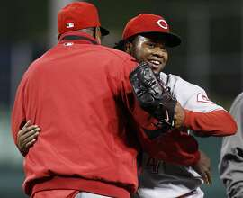 Cincinnati Reds pitcher Johnny Cueto, right, gets a hug from Reds manager Dusty Baker after getting the final out in the ninth inning against the Pittsburgh Pirates in a baseball game in Pittsburgh Tuesday, May 11, 2010. Cueto pitched a complete game, one-hit, shutout with the Reds winning 9-0.