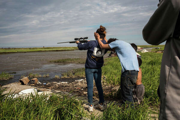 NEWTOK, AK - JULY 03: Yupik children shoot a rifle on July 3, 2015 in Newtok, Alaska. Newtok is one of several remote Alaskan villages that is being forced to relocate due to warming tempertures which is causing the melting of permafrost, widening of rivers and the erosion of land and coastline.